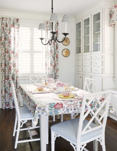 breakfast room, white dining chairs, white and blue stripped chair cushions, white storage, floral curtains and table top