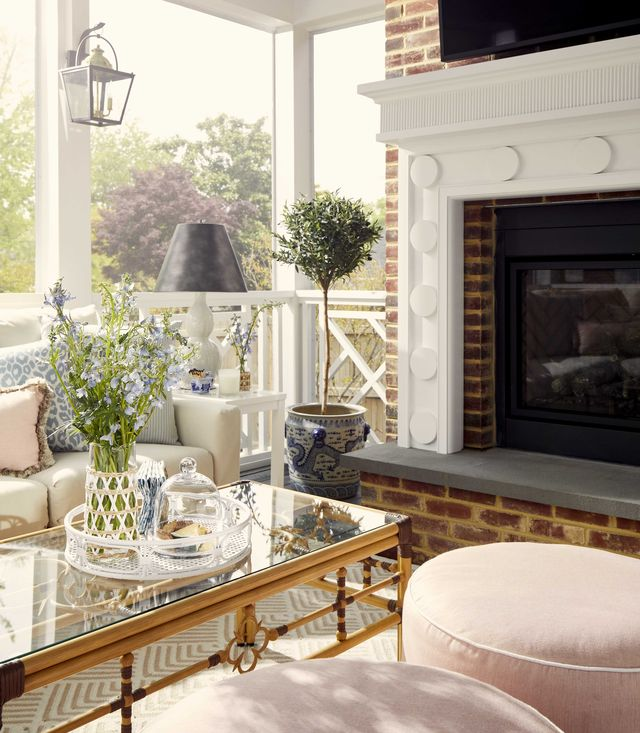 outdoor screened porch, fire place, pink ottomans, gold and glass coffee table