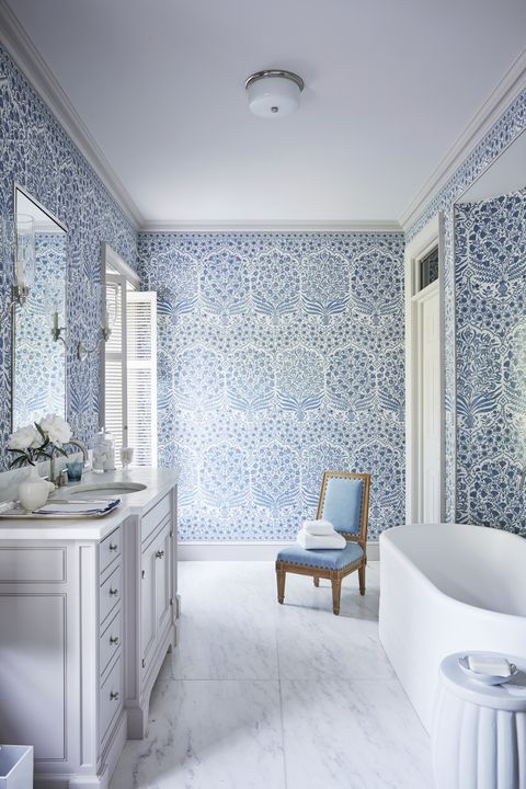 a blue and white bathroom with a large soaking tub
