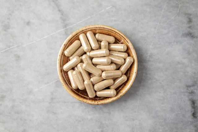 ashwagandha withania somnifera capsules concept for a healthy dietary supplementation bright stone background top view copy space