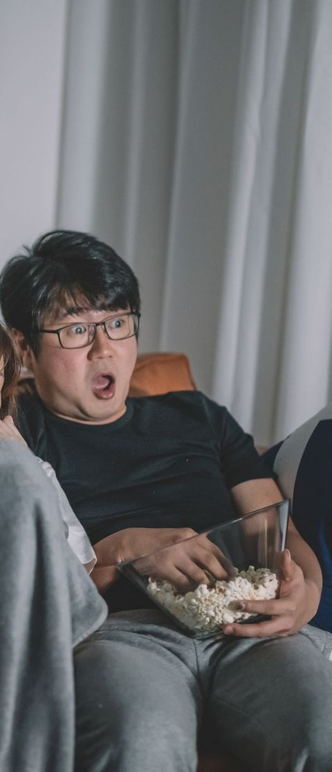 asian chinese couple watching scary horror tv show at night during weekend in living room sitting on sofa