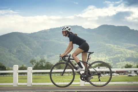 asian healthy cyclist girl wearing helmet cycling and exercise on bicycle in sprint track and open road