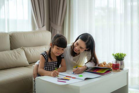 asian mother playing with her daughter drawing together with color pencils at table in living room at home parenthood or love and bonding expression concept