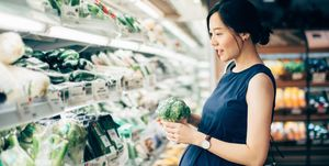Asian pregnant woman grocery shopping at the vegetable aisle in supermarket