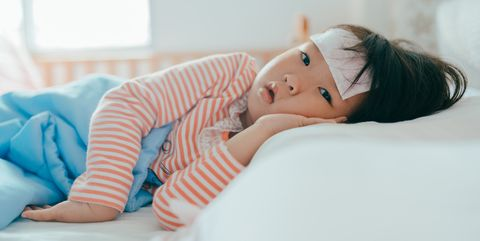 Asian sick little girl lying in bed with a high fever