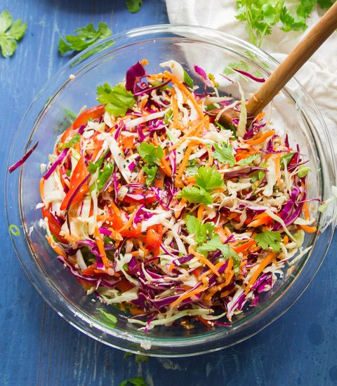 asian slaw in glass bowl with wooden spoon