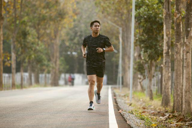 asian sportman jogging and checking smart watch between workout jogging outdoor