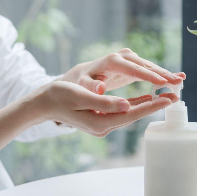 asian woman applying hand cream
