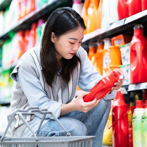 asian woman buys washing powder in supermarket