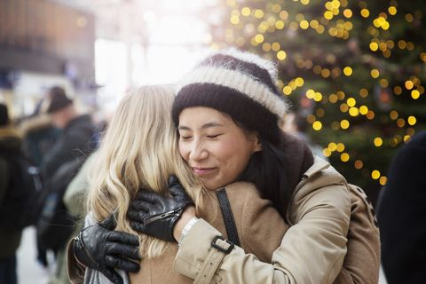Asian woman embraces friend in railroad station, christmas tree in background.