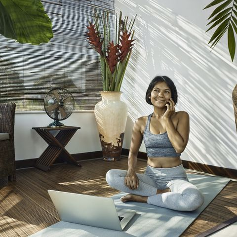 asian woman using mobile phone during home workout on open, sunny veranda