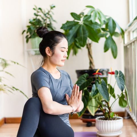 asian young woman practicing yoga in the living room
