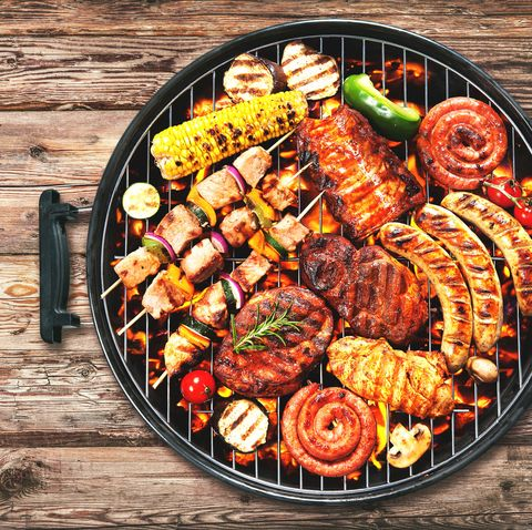 Assorted delicious grilled meat and bratwurst with vegetables on grill