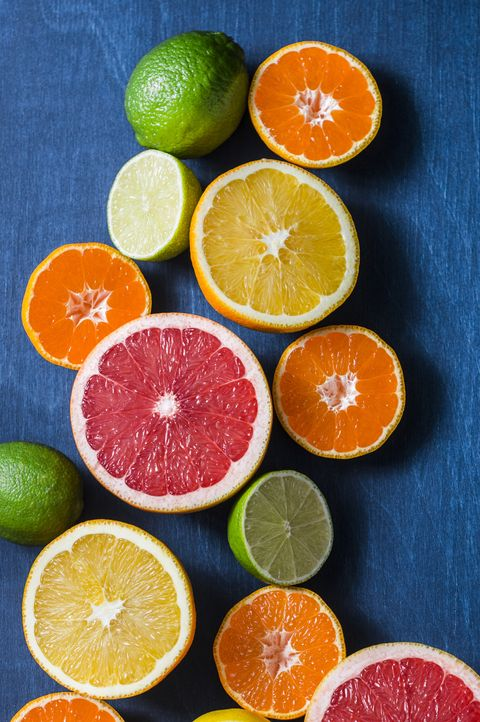 Assortment of citrus fruits on a blue background, top view. Oranges, grapefruit, tangerine, lime, lemon - organic fruits, vegetarian healthy food concept