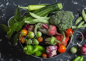 Assortment of fresh vegetables in a metal basket