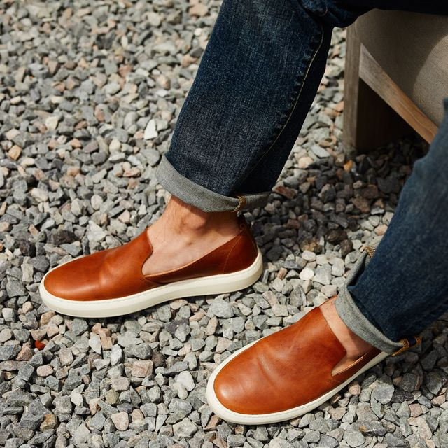 brown sneakers and blue jeans on model against gravel background