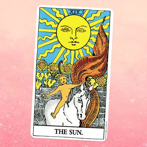 the tarot card for the sun, showing a nude androgynous young child with blonde hair sitting on a white horse, with a giant sun and a field of sunflowers behind gthem