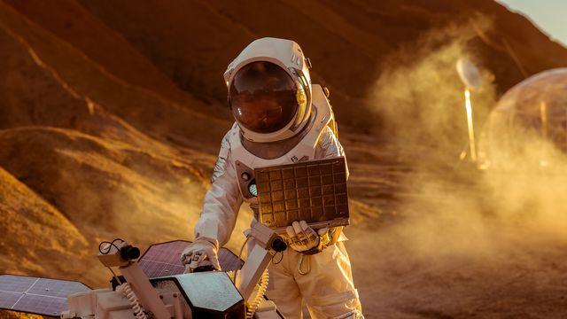 astronaut in the space suit works on laptop, adjusting rover for mars further mars explorationspace exploration conceptfirst manned mission on red planet