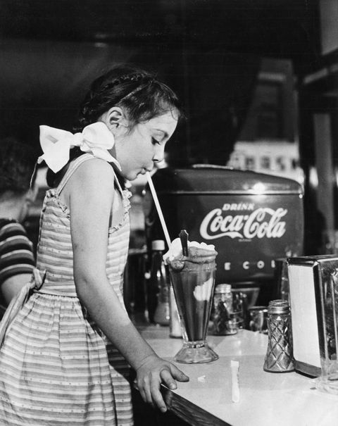 At The United States, In A Drugstore, A Little Girl Savoures An Ice Cream In 1950.