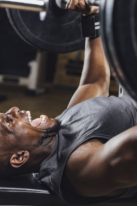 Athlete in gym doing weight lifting