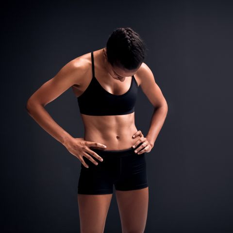 athlete standing with hands on hip against black background