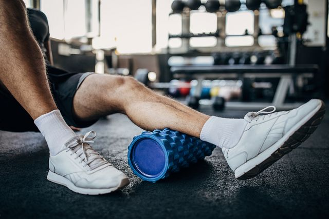 piernas de un corredor usando el rodillo miofascial