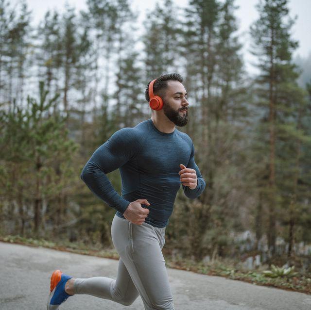 athlete with wireless headphones running outdoor