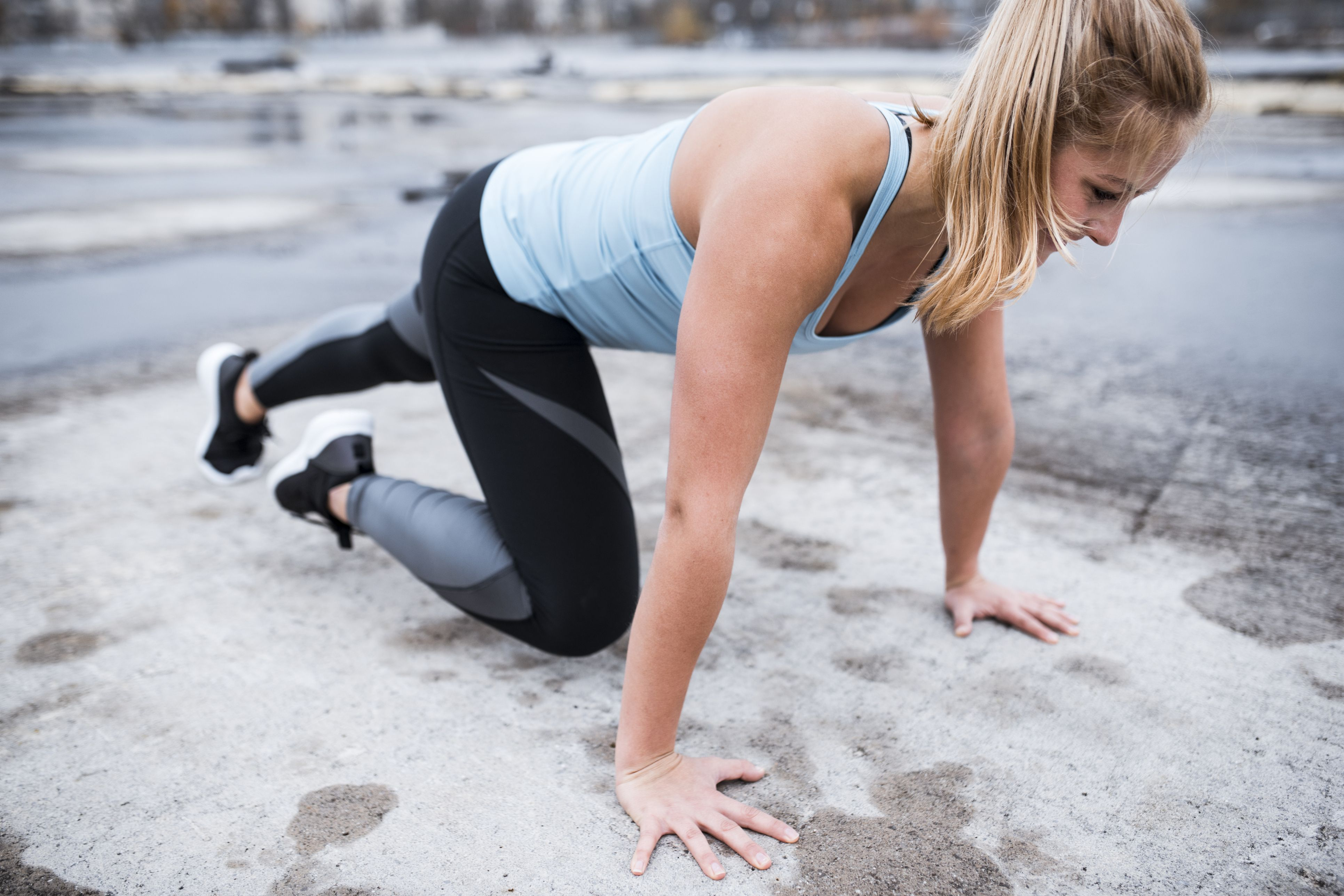 Athlete woman doing mountain climbers outdoors