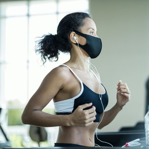 athlete workout exercise at gym after pandemic reopening they are running on treadmill and wearing protect facemask during virus protection