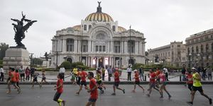 Corredores corriendo en el Maratón de México ante el Palacio de Bellas Artes