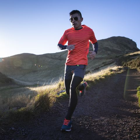Athletic cross-country runner with sun rising over rugged landscape.
