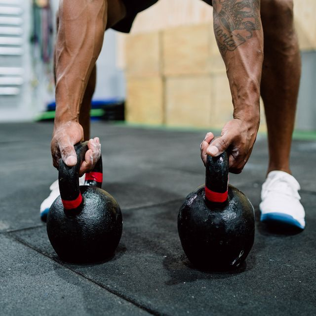 Athletic man doing exercise with gym kettlebel.