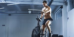 Athletic man doing HIIT workout on airbike at gym