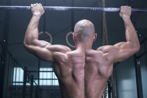 athletic man exercising chin ups in a health club