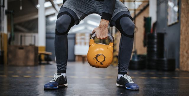 athletic man exercising with kettlebell