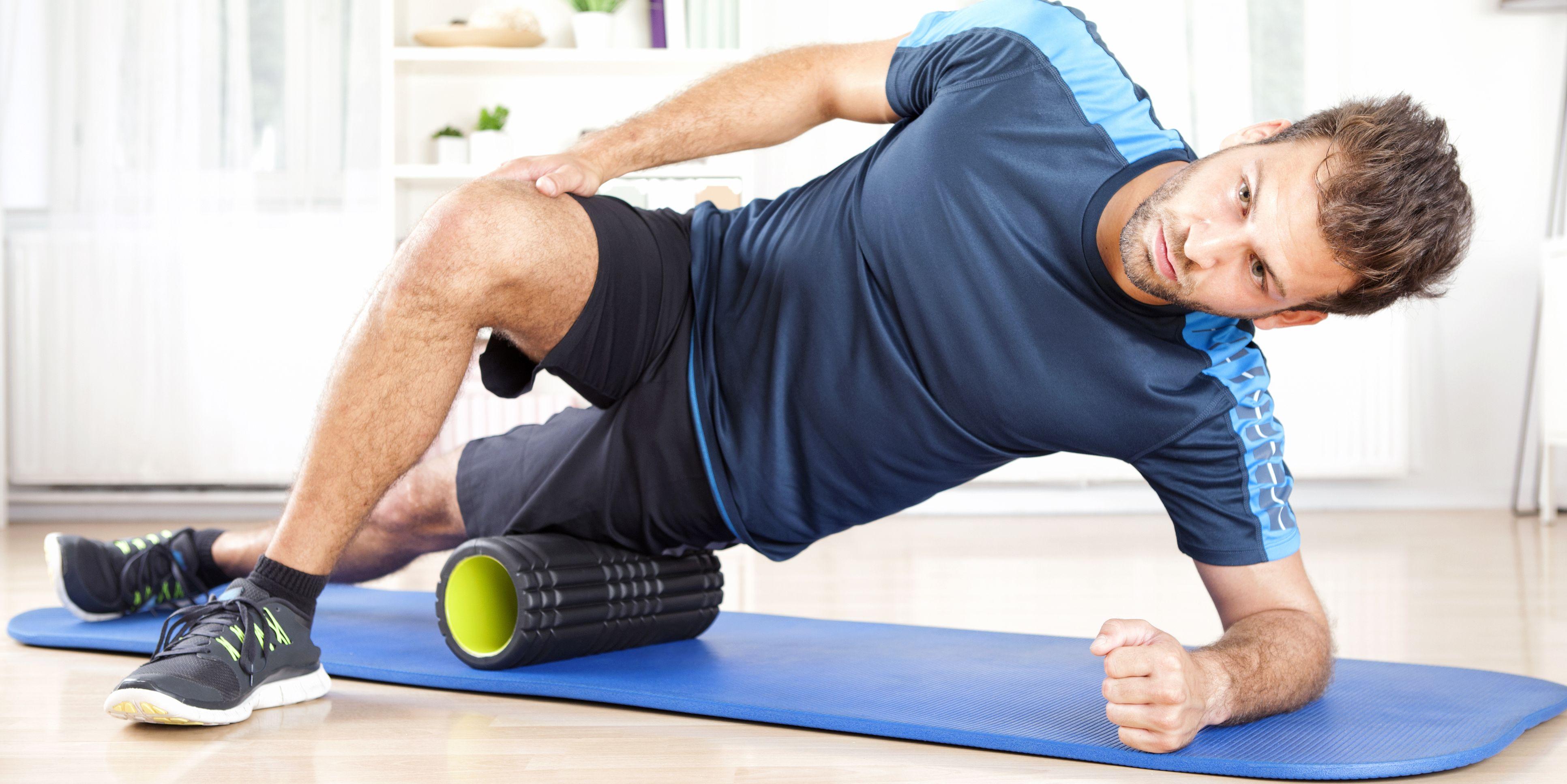 Athletic Man in Side Planking Using Foam Roller