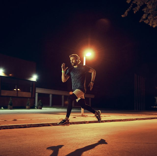 athletic man running late night in the city