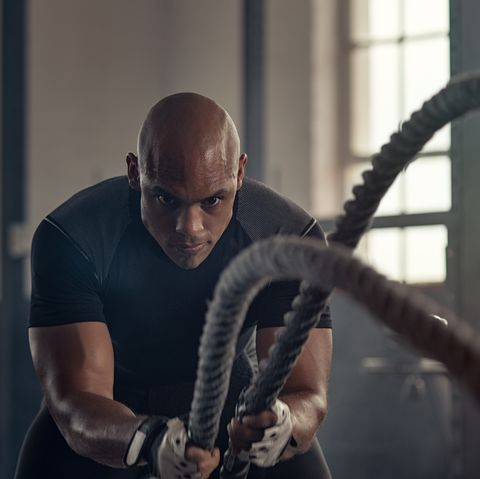 athletic man using battle rope at gym