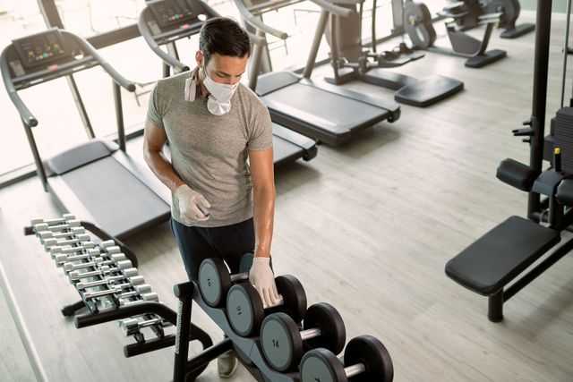 athletic man with protective face mask cleaning dumbbells with disinfectant in health club
