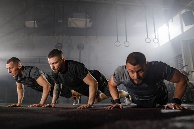 athletic men exercising push ups in a gym