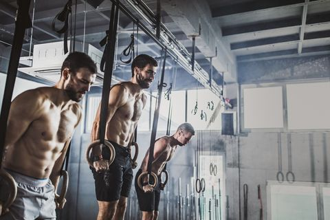 Athletic men having strength training on gymnastic rings in a gym.