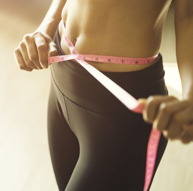 athletic slim woman measuring her waist by measure tape after diet and workout at gym