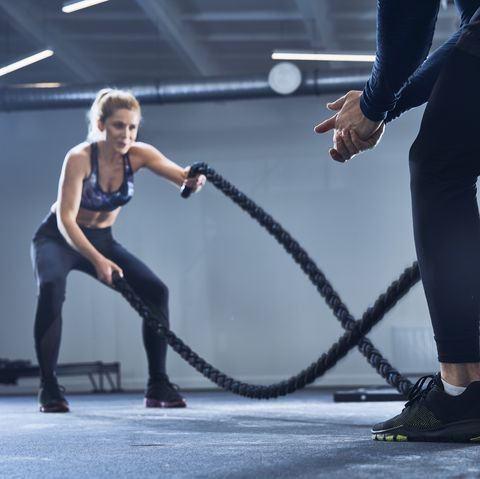 Athletic woman doing battlerope exercise with personal trainer at gym