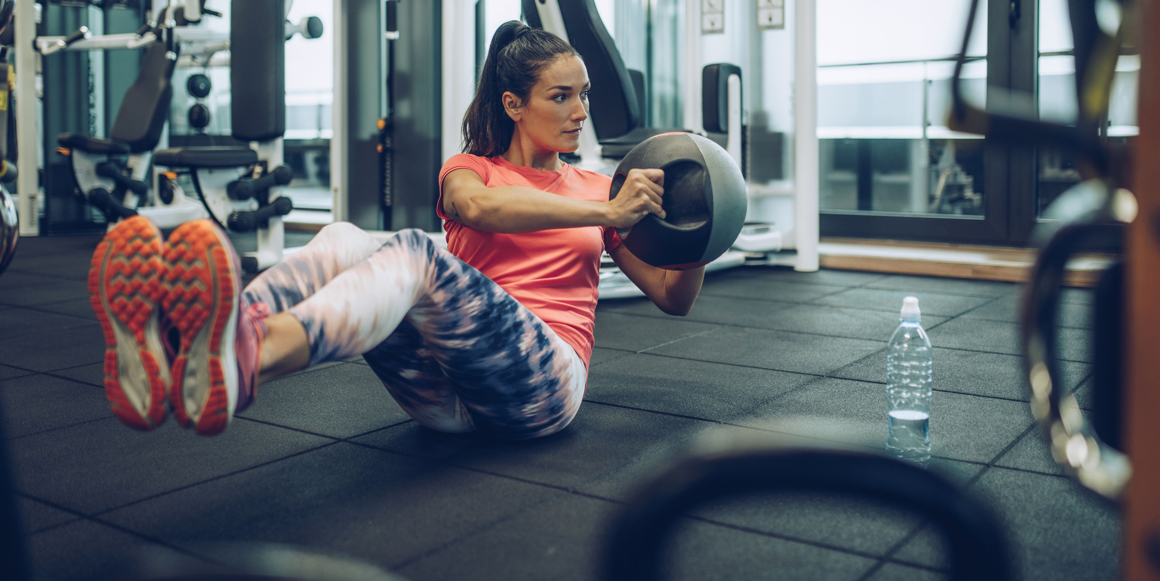 Athletic woman exercising sit-ups with medicine ball in a health club.