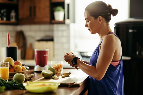 athletic woman slicing fruit while preparing smoothie in the kitchen
