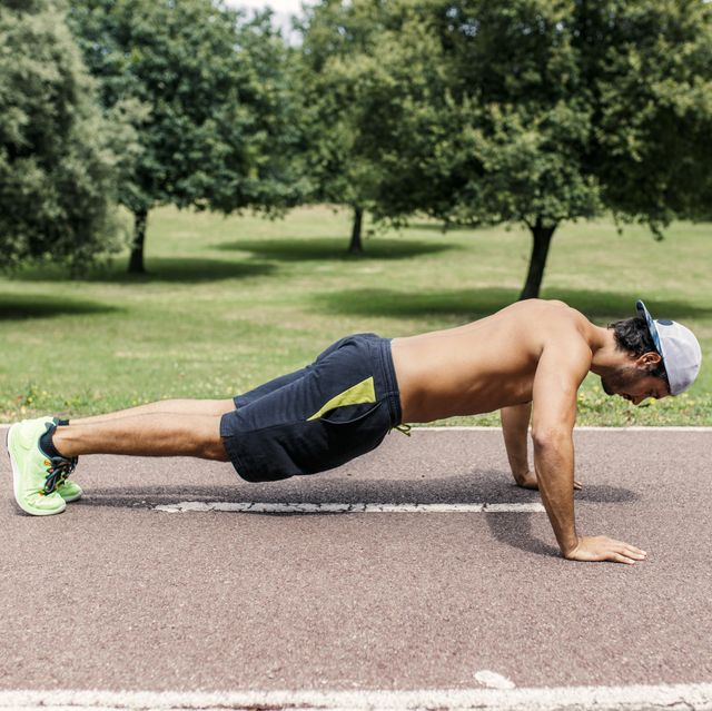 Athletic young man doing pushups in the park