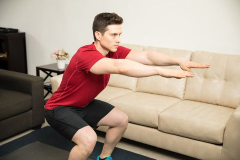 athletic young man exercising at home