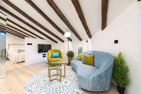 salón abuhardillado con vigas de madera vistas abierto al dormitorio