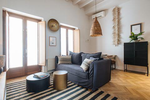 salón con sofá tapizado en negro, alfombra de rayas de fibras, mesas auxiliares de diseño circular en bloque y lámpara de techo de fibras