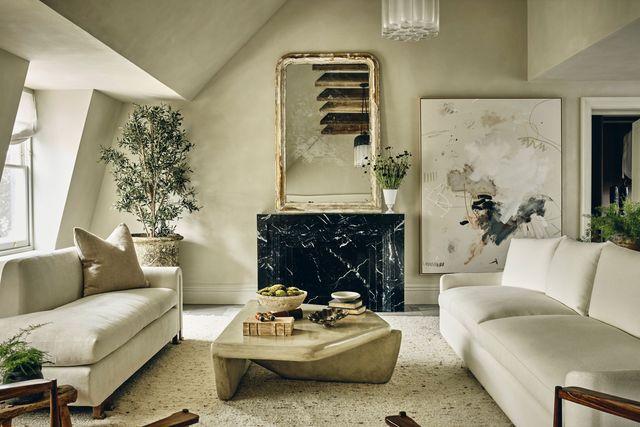 un ático decorado en tonos verde y beige con muebles de madera antiguos y contemporáneos complementado con obras de arte